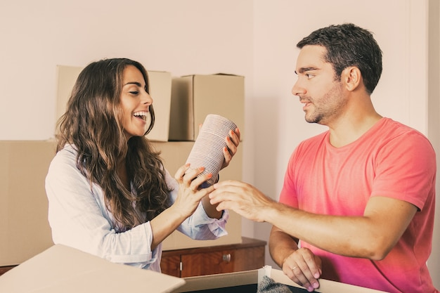 Happy excited young man and woman moving and unpacking things, getting out objects from open carton box