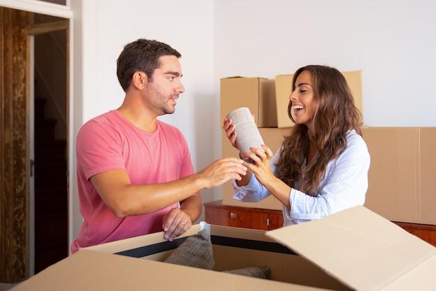 Felice eccitato giovane uomo e donna che si muovono e disimballano cose, tirando fuori oggetti da una scatola di cartone aperta