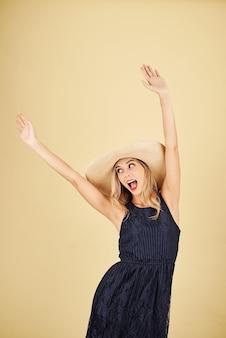 밀짚 모자 춤에 행복 한 흥분된 젊은 세련 된 여자