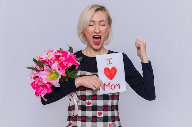 Giovane donna felice ed emozionata in bello vestito che tiene la cartolina d'auguri e bouquet di fiori stringendo il pugno urlando che celebra la giornata internazionale della donna in piedi sopra il muro bianco