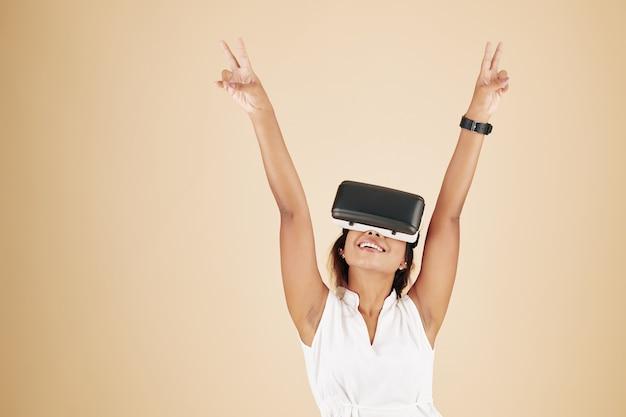 ベージュで隔離の仮想現実のヘルメットで踊る幸せな興奮した若い女性