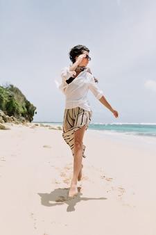 Felice eccitata giovane donna vestita pantaloni a righe, camicia bianca e occhiali che salta sulla spiaggia con sabbia bianca vicino all'oceano