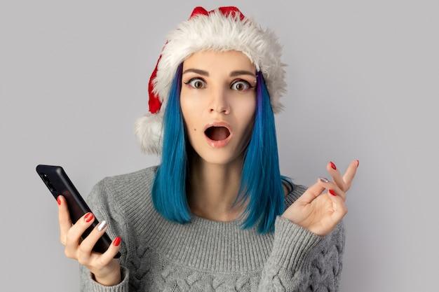 회색 배경 위에 스마트 폰으로 산타 모자에 행복 한 흥분된 젊은 여자. 크리스마스 온라인 쇼핑 판매 개념