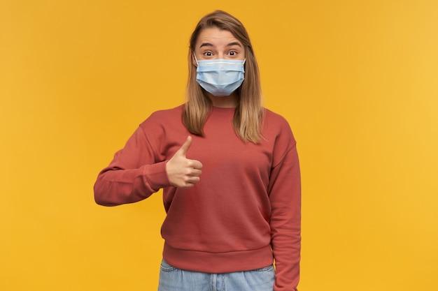 立って、黄色の壁の上に孤立して親指を見せてコロナウイルスに対する顔のウイルス保護マスクで幸せな興奮した若い女性