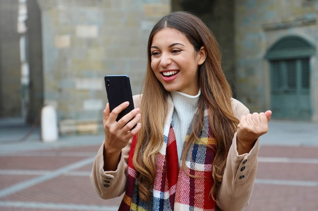 Happy excited young woman laughs watching good news on mobile phone with fist up in city street, winter time