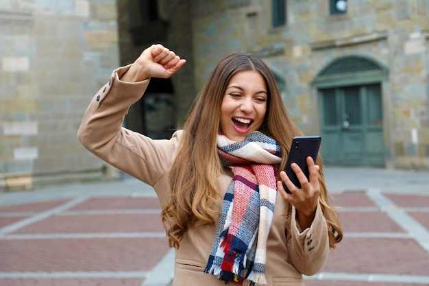 Happy excited young woman laughs watching good news on mobile phone with raised arm in city street, winter time