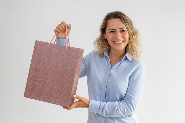 Happy excited young woman showing bright shopping bag