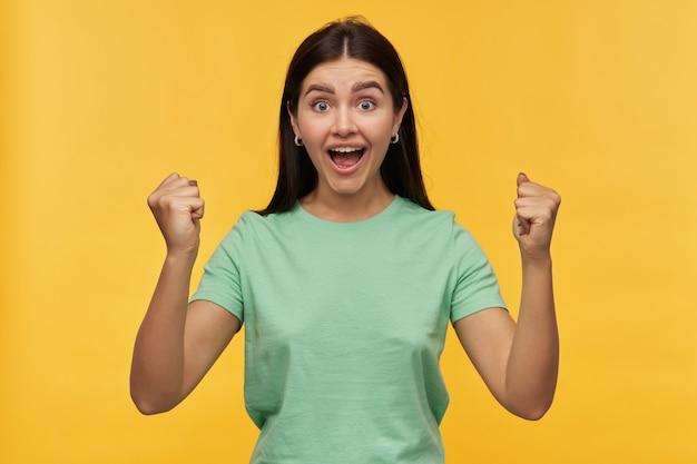 黒い髪とミントの t シャツで手を上げた幸せな興奮した若い女性が叫び、黄色の壁に分離された成功を祝う
