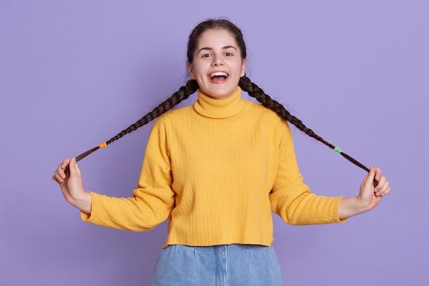 暗い長い髪の幸せな興奮している若い女性、おさげ髪を保持し、キューを脇に広げて
