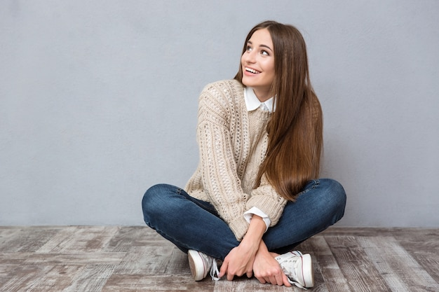 Happy excited young woman with long hair in beige sweater and jeans sitting on wooden floor with legs crossed and looking away