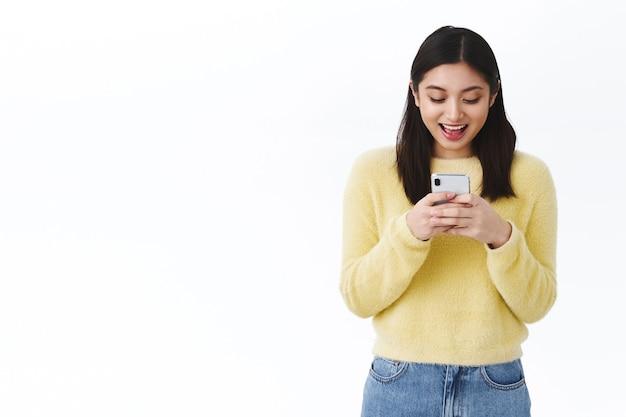 새로운 스마트폰 게임을 하고, 휴대전화를 들고, 온라인에서 비디오를 보고, 친구에게 문자를 보내고, 인터넷에서 의사소통을 하며 즐겁게 웃는 얼굴로 화면을 바라보는 행복한 흥미진진한 아시아 소녀