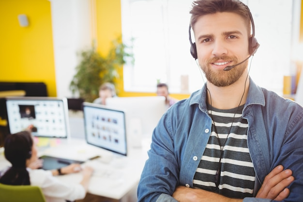 Happy executive wearing headphones at creative office