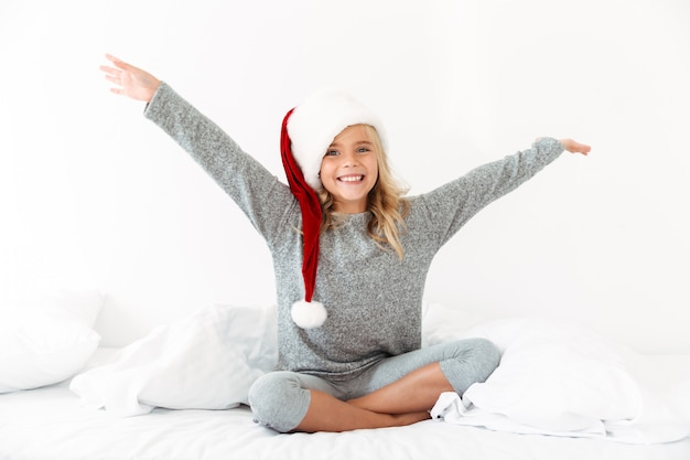 Happy exited blonde girl in santa's hat sitting on bed with raised arms,