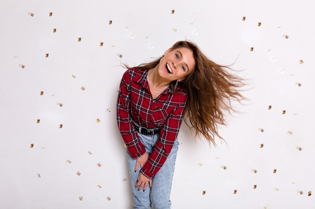 幸せな出口の素敵な女性は、カジュアルな服装で紙吹雪と白い壁の上で楽しんで踊っています。落ちた紙の心を見て笑っている興奮した女性。