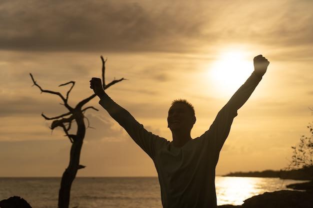 Счастливый вышел человек, полный положительных эмоций на море и фоне красивого восхода солнца. концепция счастья, радости и успеха.