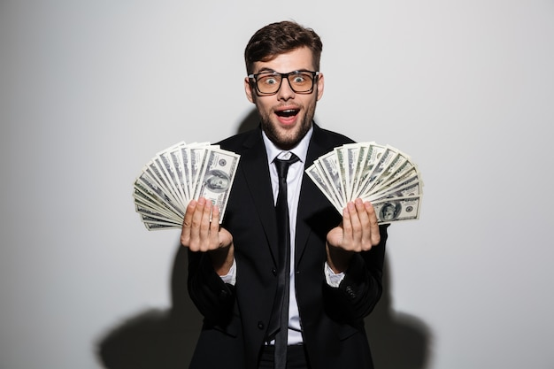 Happy exited man in glasses and black suit holding two bunches of money