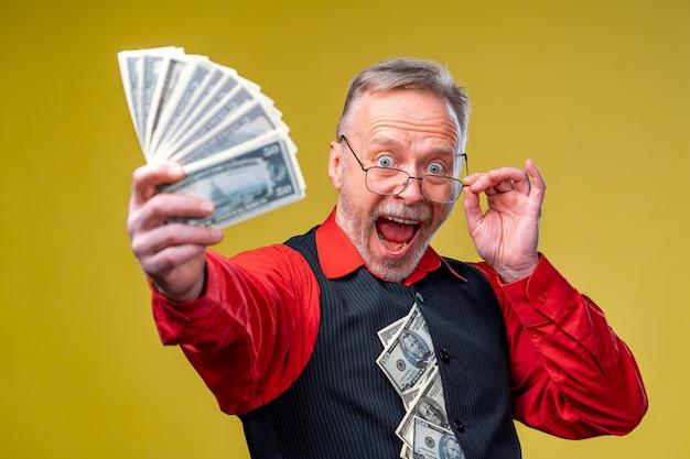たくさんのお金を持っている眼鏡と赤いシャツを着た幸せな出口の男