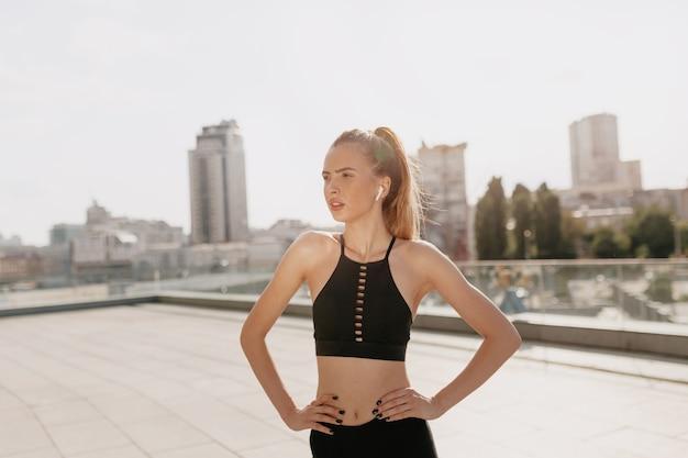 Felice donna motivata uscita di formazione con le cuffie fuori nella soleggiata giornata estiva sulla città. donna europea di stile di vita attivo sano che si esercita all'aperto.