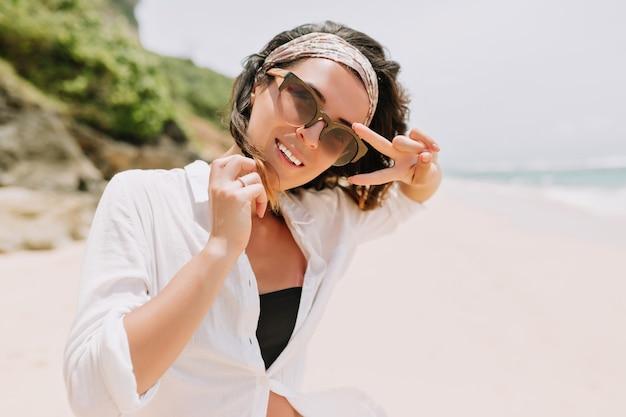 어두운 물결 모양의 머리를 가진 행복한 종료 된 젊은 여자는 검은 색 안경을 착용하고 흰 셔츠에 머리 장식은 햇빛에 하얀 모래 해변을 산책합니다.
