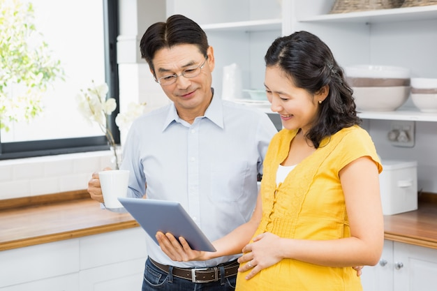Happy expectant couple using tablet in the kitchen