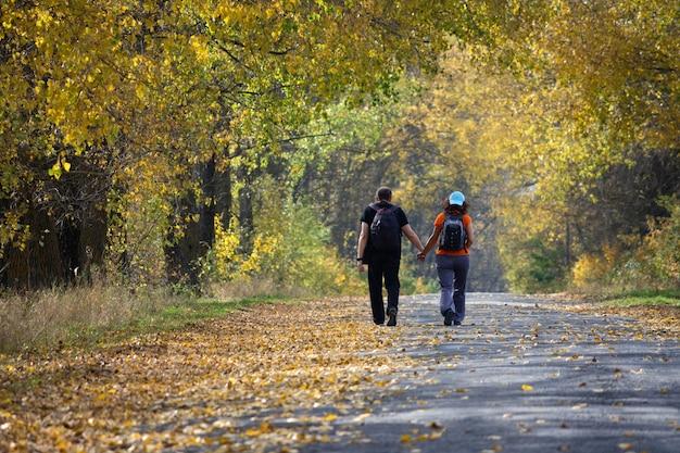 秋の森を歩く幸せな妊娠中の両親