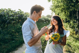 Happy expecting couple blows soap balloons standing on the field full of yellow sunflowers
