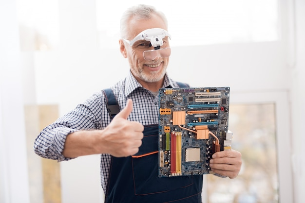 Happy experienced engineer is holding motherboard.