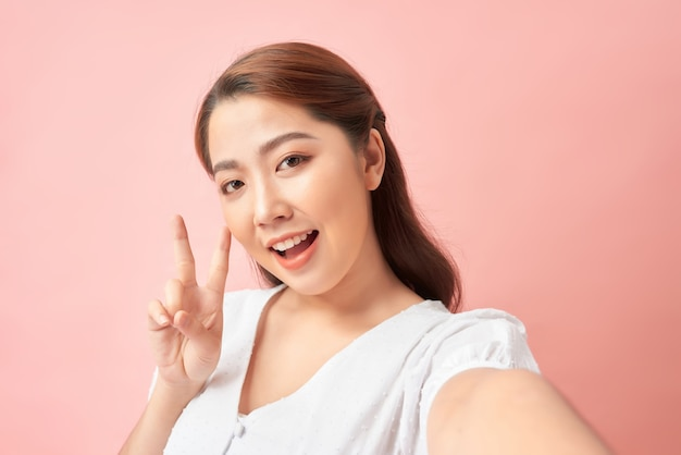 Счастливая выразительная молодая женщина позирует, фотографируя себя через мобильный телефон, над розовым