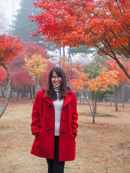 Happy eyeglasses asian woman in red coat standing in cold colorful autumn trees garden park