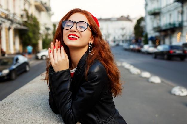 通りでスタイリッシュな赤いベレー帽で幸せな素晴らしい生姜女