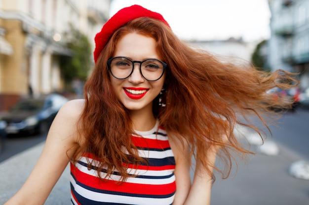 Happy fabulous ginger woman in stylish red beret in the street