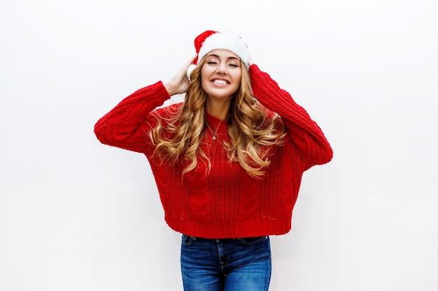 笑顔。赤い仮面舞踏会の新年の帽子とセーターの恍惚とした女性