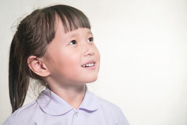 幸せそうな顔の制服を着た小さなアジアの学校の女の子