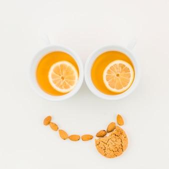 レモンティーカップで作った幸せそうな顔。アーモンドと白い背景の上のクッキーを食べた