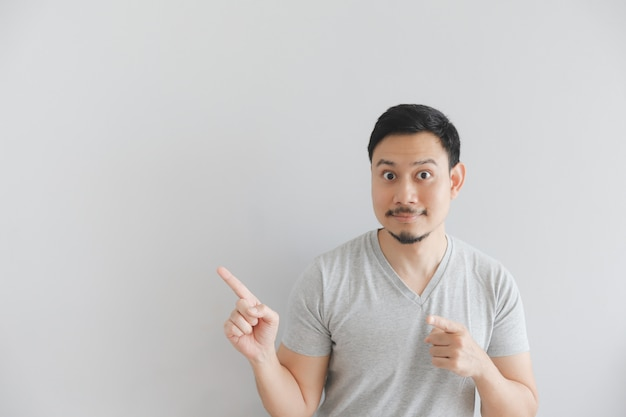 Happy face of man in grey t-shirt with hand point on empty space.