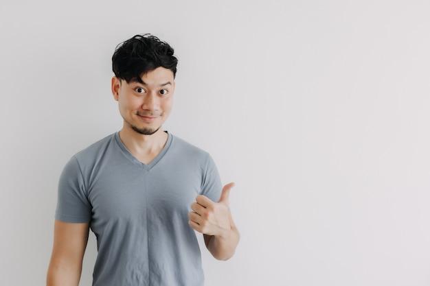 Счастливое лицо азиатского мужчины смотрит на пустое пространство, изолированное на белой стене