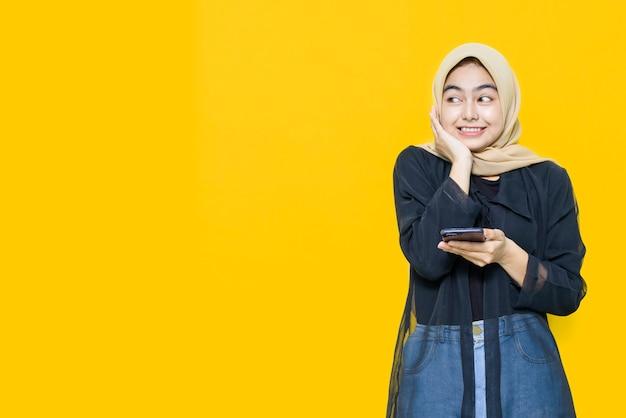 Счастливое лицо молодой азиатской женщины с смартфон на желтой стене