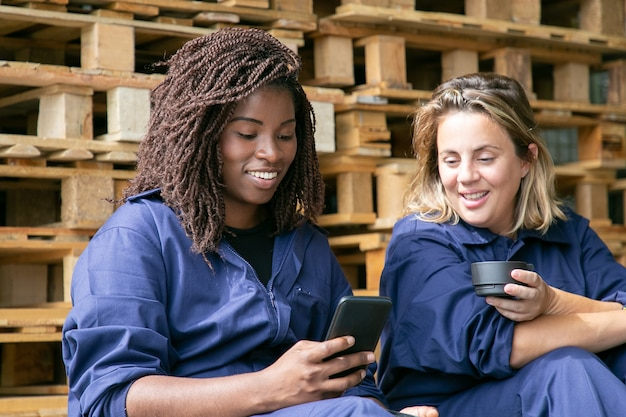 Happy factory colleagues in overalls watching content on cellphone together while drinking coffee in warehouse