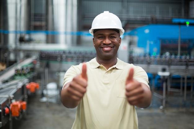 ドリンク製造工場で彼の親指を現して幸せな工場労働者