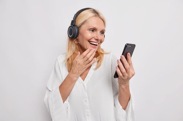 幸せな金髪の大人の女性がオンラインで電話をかけるスマートフォンとヘッドフォンを使用して親友が新しい技術を学ぶのを聞いてうれしい白いスタジオの壁に隔離されたモバイルデバイスでビデオを見る