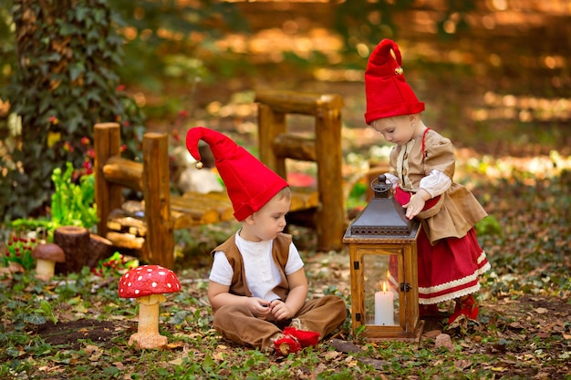 Happy fairytale baby gnome girl and boy playing in the forest
