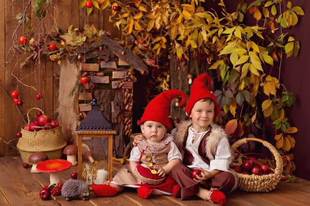 Счастливые сказочные маленькие гномы девочка и мальчик играют и собирают тыквы, едят яблоки
