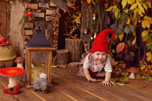 Счастливая сказочная маленькая девочка-гном играет и собирает тыквы, грибы, ест яблоки
