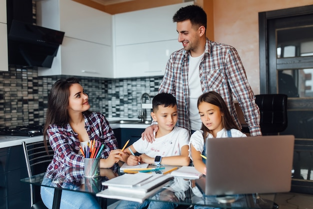 Happy familly, brunette mother with father and their adorable children doing homework for school