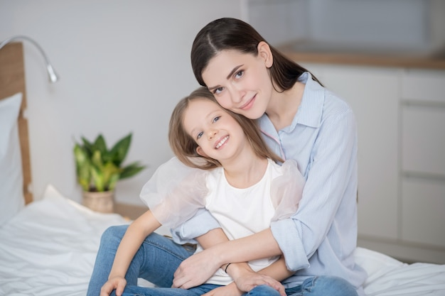 Счастливая семья. красивая женщина обнимает свою дочь и выглядит счастливой