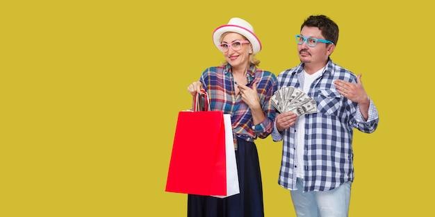 買い物の後の幸せな家族、一緒に立っているカジュアルな市松模様のシャツの大人の男性と女性、歯を見せる笑顔で紙袋を持っている妻、大きなスポンサーのようなお金の夫のファン。屋内、孤立した、スタジオショット