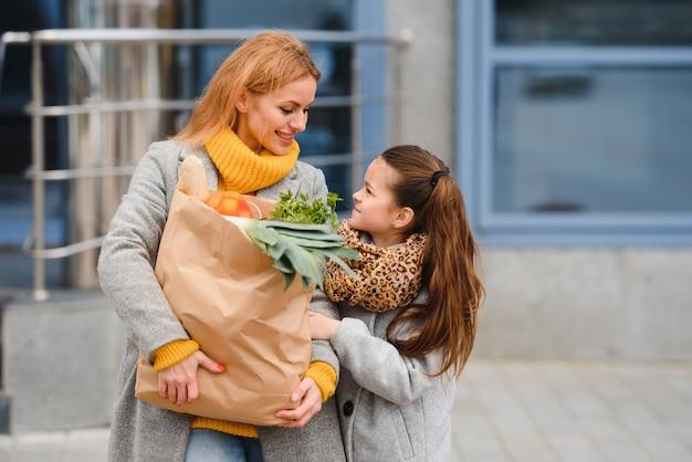 Счастливая семья после покупок с хозяйственными сумками на парковке возле торгового центра. мама с дочкой.