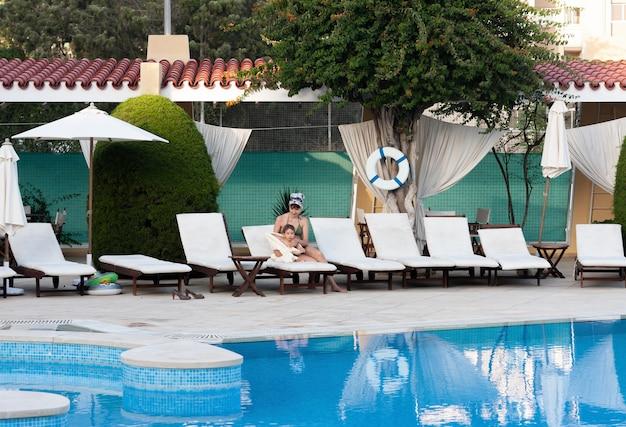 幸せな家族と健康的なライフスタイル。プールの近くに小さな子供を持つ若い母親がリゾートで休んでいます
