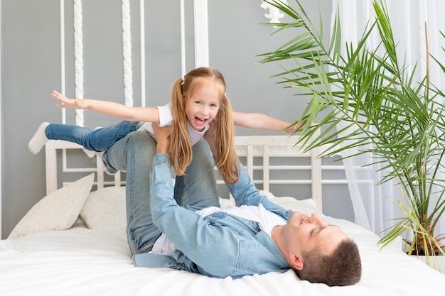 행복한 가족과 집에서 침대에서 아버지와 딸과 함께 시간을 보내고 비행기처럼 날아 다니며 팔을 옆으로 벌리고 프리미엄 사진