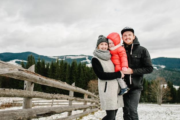 Счастливая семья веселится и играет снежной зимой, гуляет по горной природе. отец, мать и дочь детей наслаждаются путешествием. морозный зимний сезон.